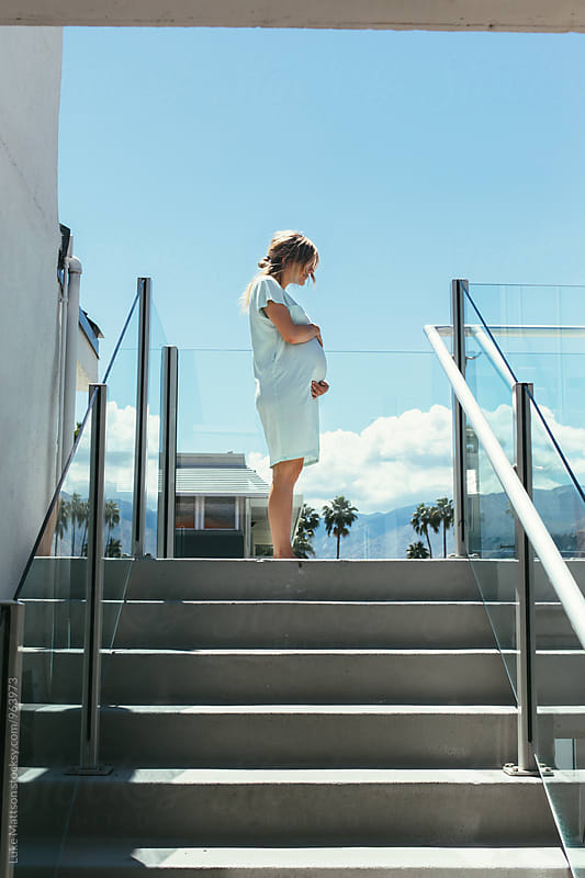 Young Pregnant Woman In Light Blue Dress Standing At Top Of Stairs On Sunny Day by Luke Mattson for Stocksy United