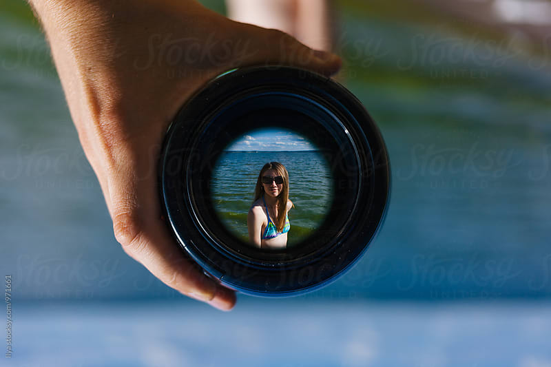 View of young woman in bikini on beach through spyglass lens  by Ilya for Stocksy United