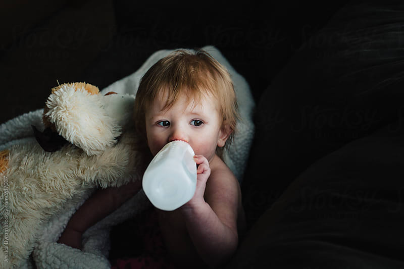 Cute baby drinking milk from a bottle and holding onto a stuffed puppy dog. by Jessica Byrum for Stocksy United