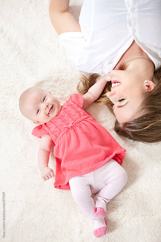 Baby: Baby Giggles While Playing on Floor by Sean Locke for Stocksy United