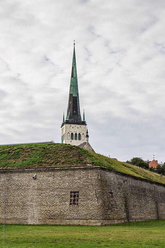 Spire of St. Olav's church (Oleviste kirik) in Tallinn is seen behind the town wall by Melanie Kintz for Stocksy United