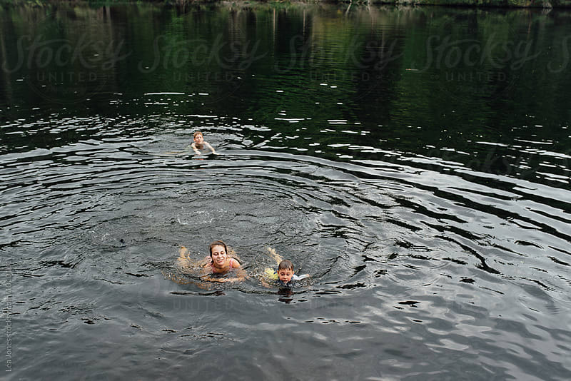kids swimming in a lake by Léa Jones for Stocksy United