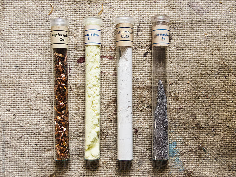 four old test tubes with different chemicals for testing on an old cloth by Melanie Kintz for Stocksy United