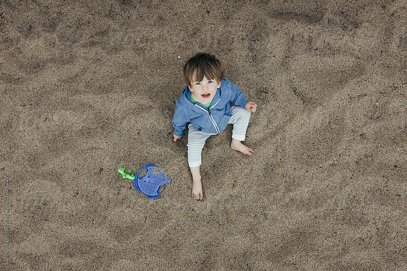 Toddler looking up at a camera while playing in a giant sandbox. by Lucas Saugen for Stocksy United
