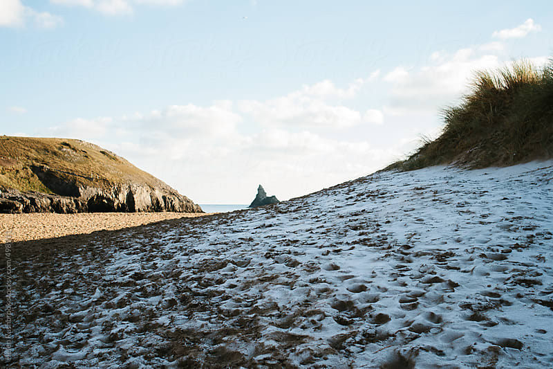 The remains of snow on a beach in winter. by Helen Rushbrook for Stocksy United