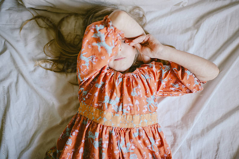 Little girl covering face laying on bed by Kristin Rogers Photography for Stocksy United