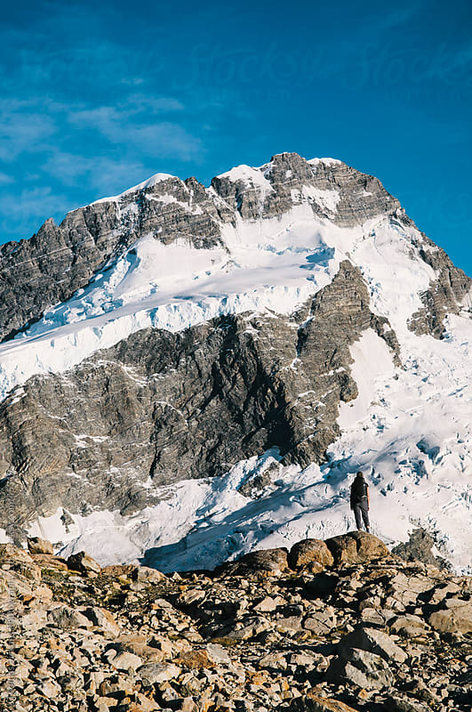 Woman standing beneath Mt Sefton, Aoraki / Mt Cook National Park by Thomas Pickard for Stocksy United