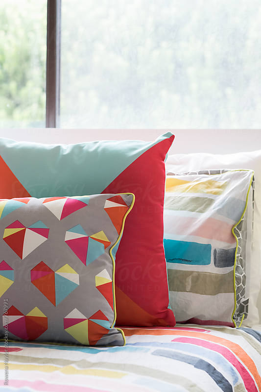 Colorful soft furnishings in bedroom by Rowena Naylor for Stocksy United