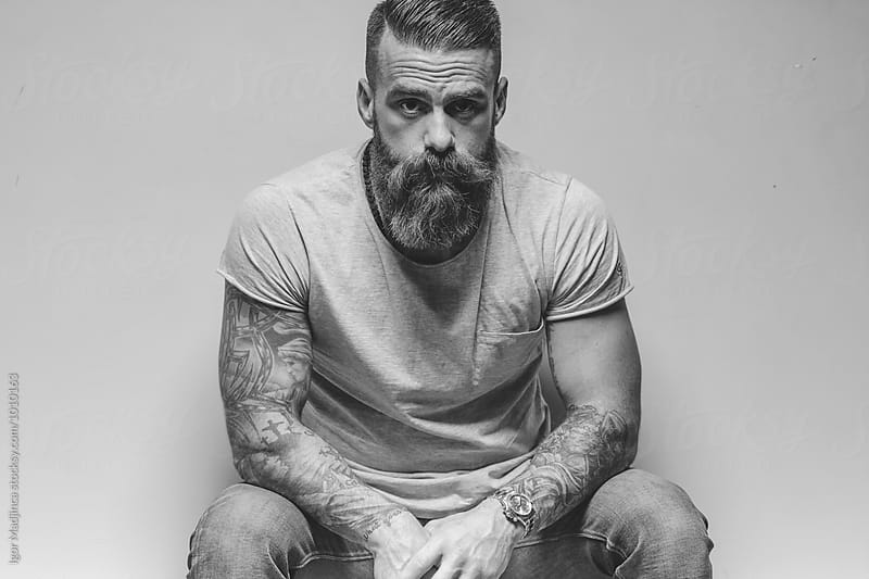 portrait of a handsome and sexy tattooed hipster mature man with a cross by Igor Madjinca for Stocksy United