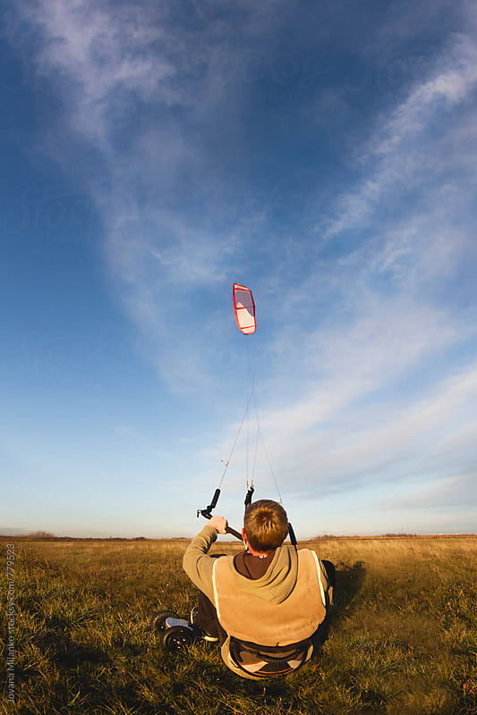 Young man kiteboarding in the field at sunset by Jovana Milanko for Stocksy United