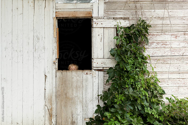 boy looks over a barn door by Kelly Knox for Stocksy United