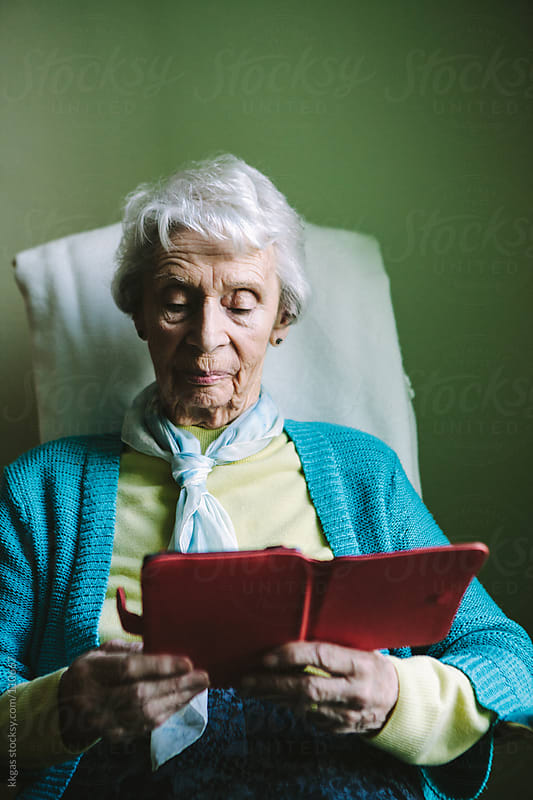 Senior woman using an e-reader by kkgas for Stocksy United