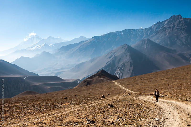 A lone woman trekking in the himalayas. by Shikhar Bhattarai for Stocksy United