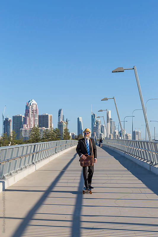 Alternative businessman skateboarding across bridge with tall buildings in background by Ben Ryan for Stocksy United