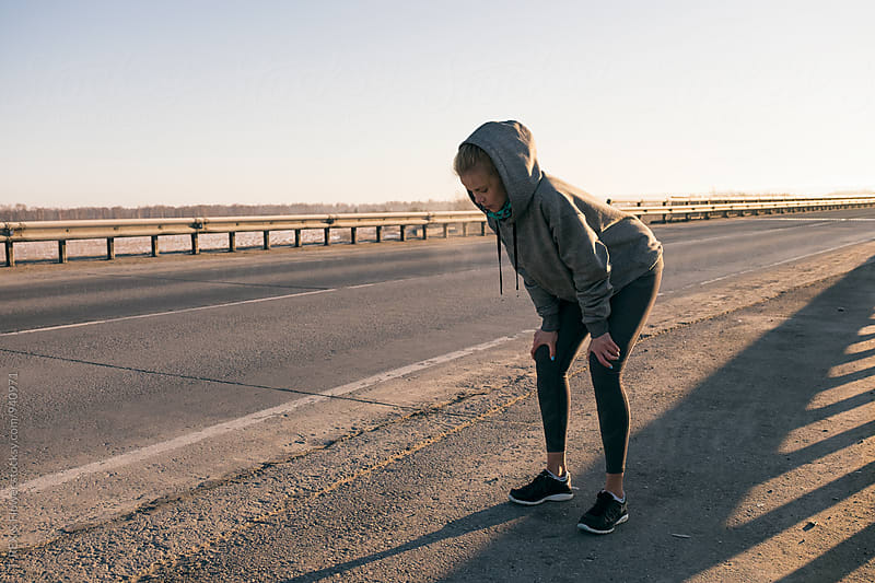 Female athlete standing on road and looking down by Danil Nevsky for Stocksy United