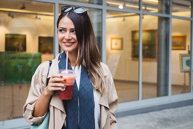 Beautiful Brunette Woman Standing on a Street While Having Smoothie  by Katarina Radovic for Stocksy United