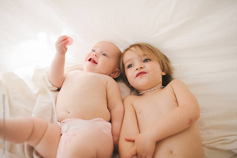brother and sister under the sheets by luke + mallory leasure for Stocksy United