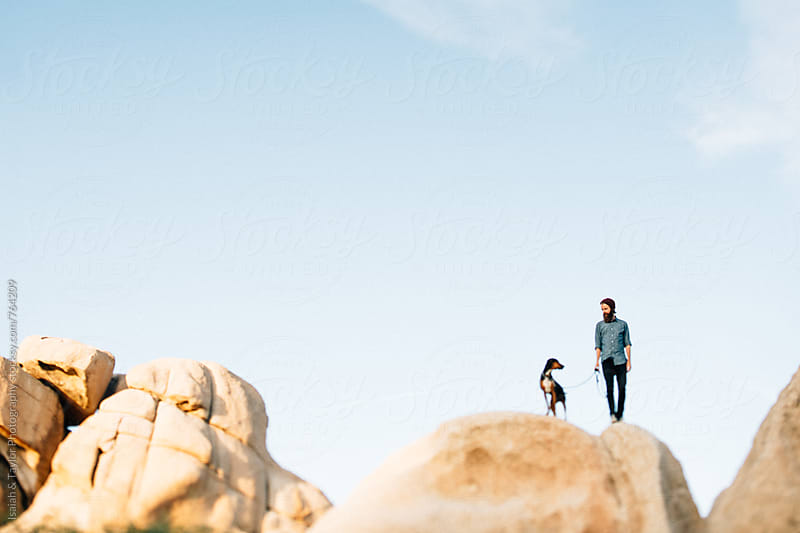 Man and dog on rock by Isaiah & Taylor Photography for Stocksy United