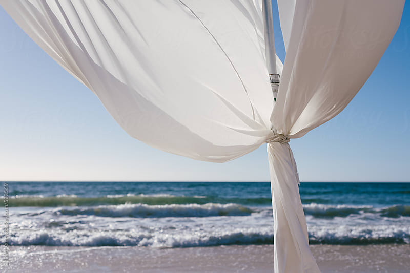 romantic beach setting with flowy white curtains by Gillian Vann for Stocksy United