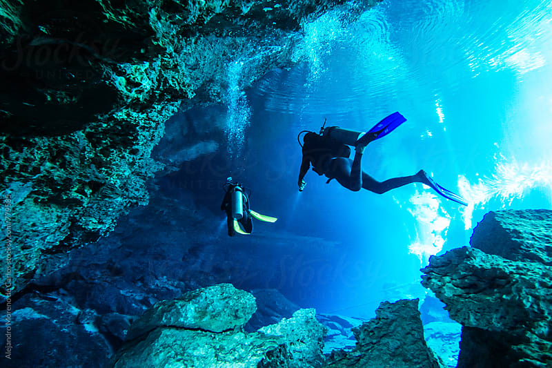 Scuba divers exploring an underwater cave in a cenote in Yucatán, Mexico by Alejandro Moreno de Carlos for Stocksy United
