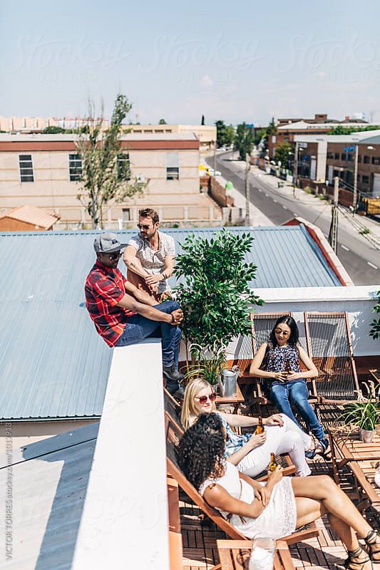 Friends Having Fun on a Summer Day in a Rooftop by Victor Torres for Stocksy United