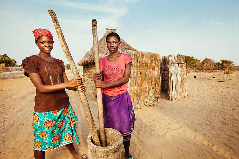 Young African Hambukushu women pounding corn/millet by Micky Wiswedel for Stocksy United
