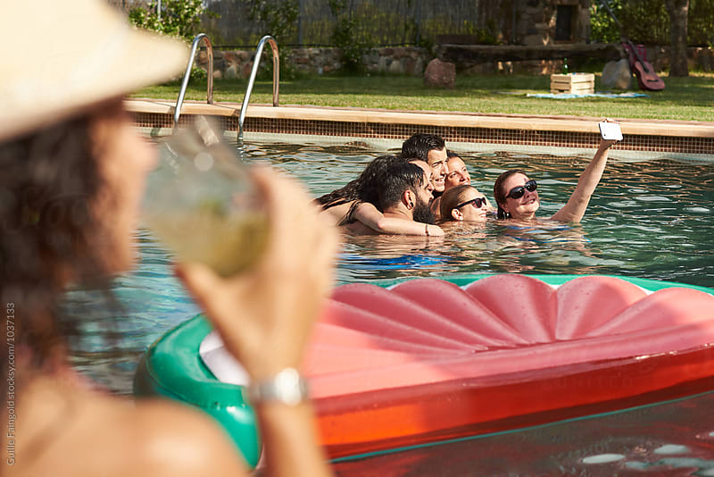Friends taking selfie in pool with inflatable watermelon by Guille Faingold for Stocksy United
