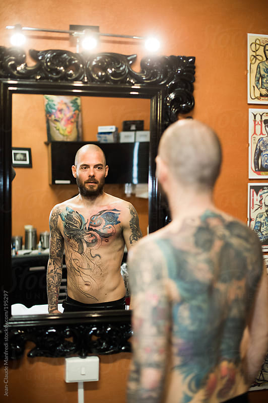 tattooed man looks in the mirror after a tattoo session by Jean-Claude Manfredi for Stocksy United