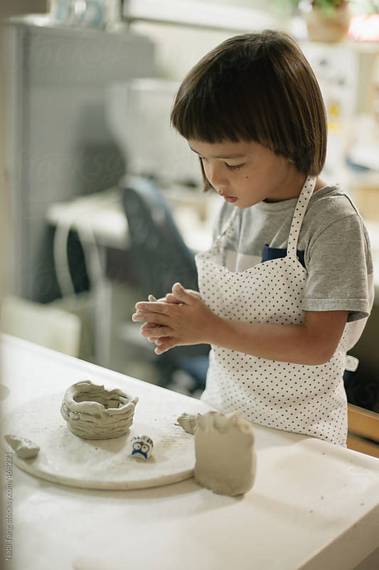A cute little Asian boy making a cup from clay alone in the ceramic studio by Nabi Tang for Stocksy United