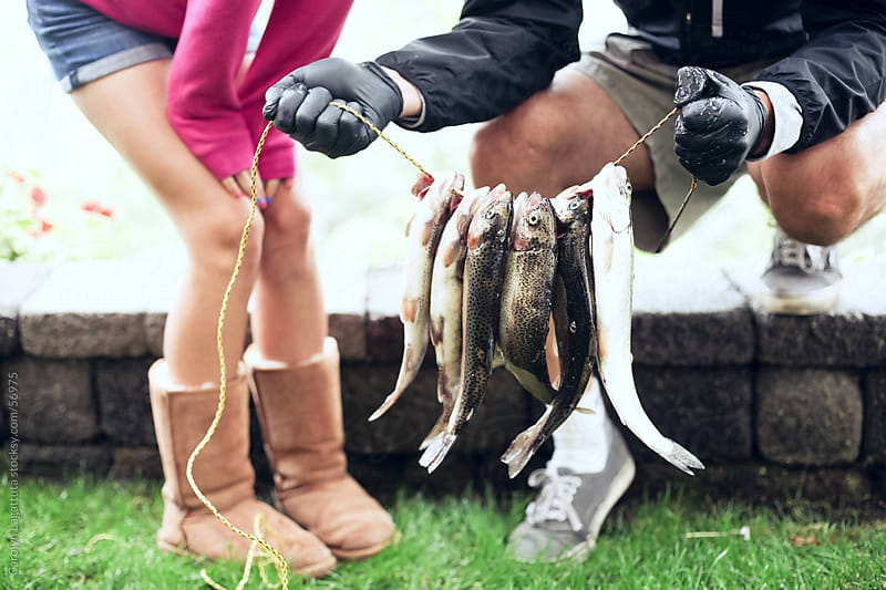 Father and daughter show off the trout they caught by Carolyn Lagattuta for Stocksy United