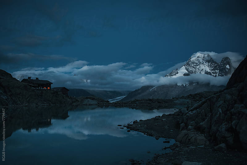 Mountain peaks and cabin reflected in the lake at dawn by RG&B Images for Stocksy United