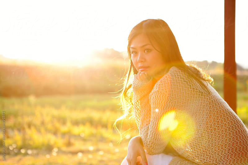 Thoughtful asian female sitting in open field by Linzy Slusher for Stocksy United