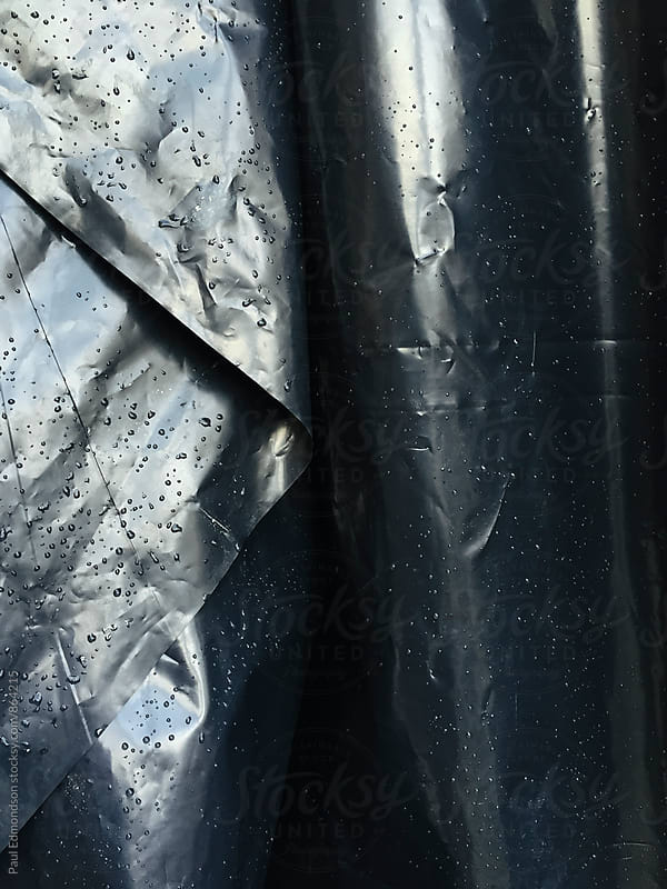 Close up of wet, black plastic sheeting covering construction site by Paul Edmondson for Stocksy United
