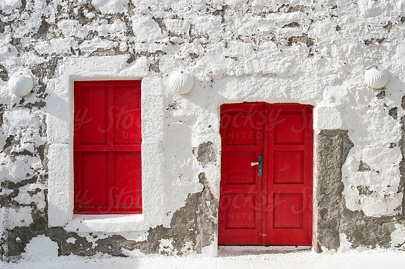 White facade with red door and window by Bisual Studio for Stocksy United