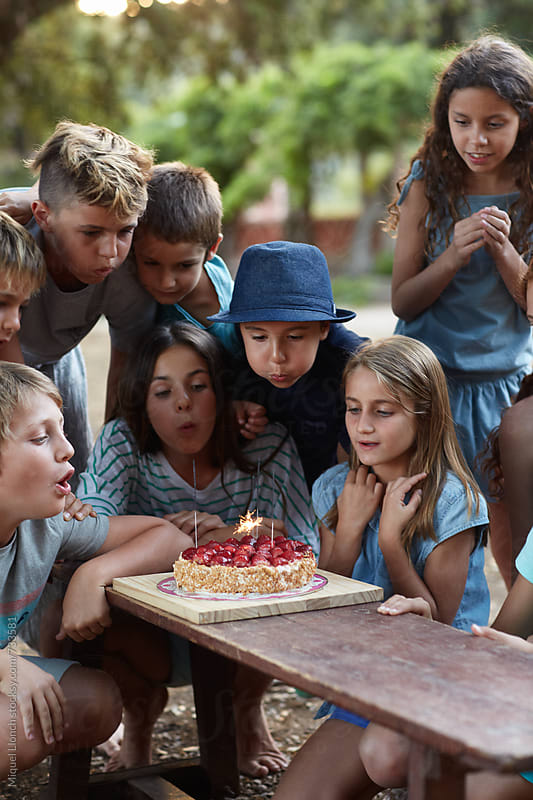 Group of children blowing the sparkles of a birthday cake by Miquel Llonch for Stocksy United