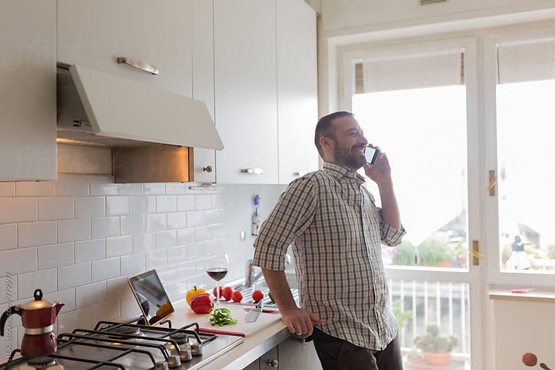 Man on the Phone while is Cooking by HEX. for Stocksy United