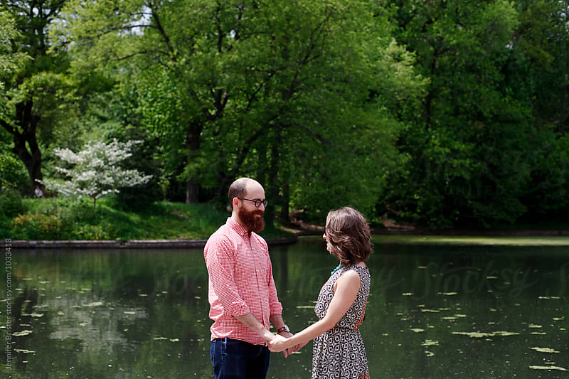 Couple holding hands in front of lake  by Jen Brister for Stocksy United