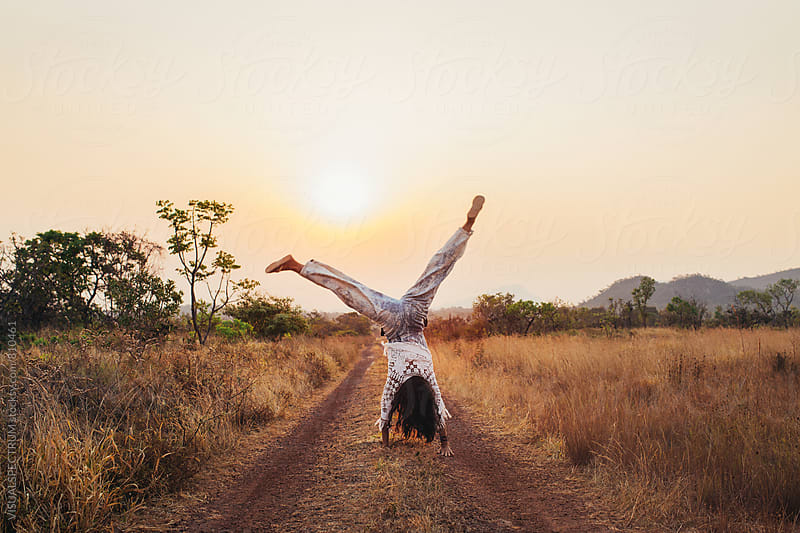 Young Woman Doing Cartwheel in Nature at Sunset Time by Julien L. Balmer for Stocksy United