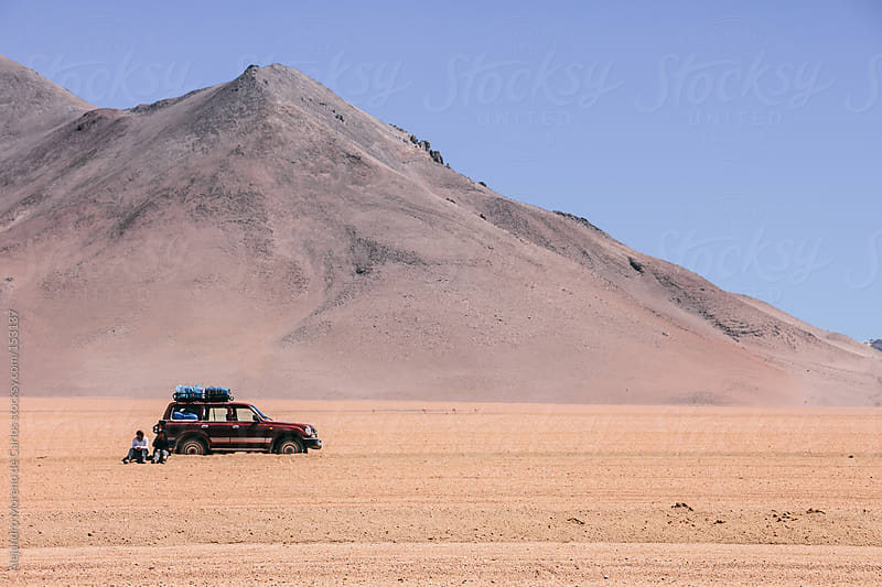 Car on desert with mountain on the background. SUV 4WD vehicle, Bolivia by Alejandro Moreno de Carlos for Stocksy United