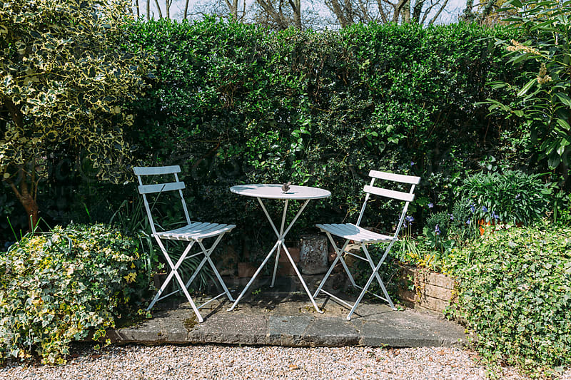 Two white garden chairs and table on a small patio in a country garden by Paul Phillips for Stocksy United