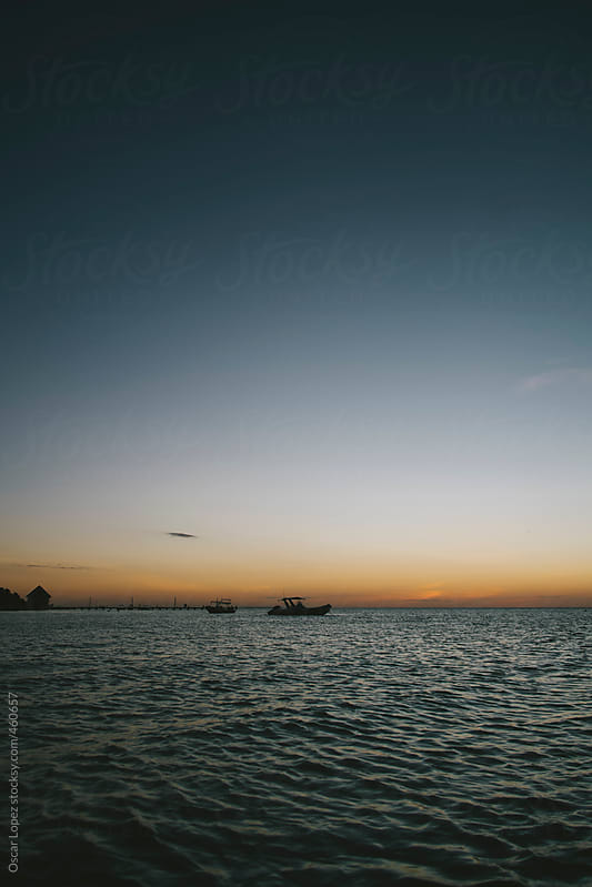 Two boat against a beautiful Belizian sunset by Oscar Lopez for Stocksy United