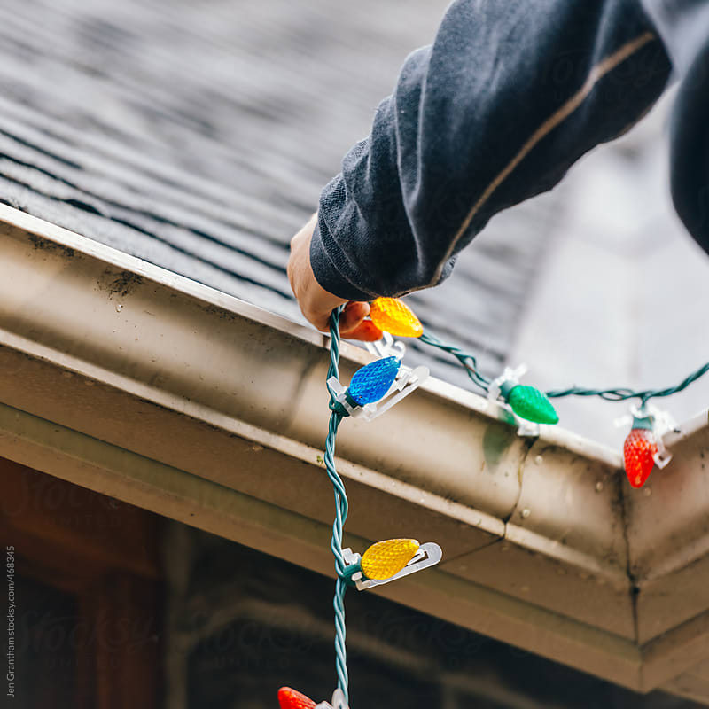 Hanging the Christmas Lights by Jen Grantham for Stocksy United