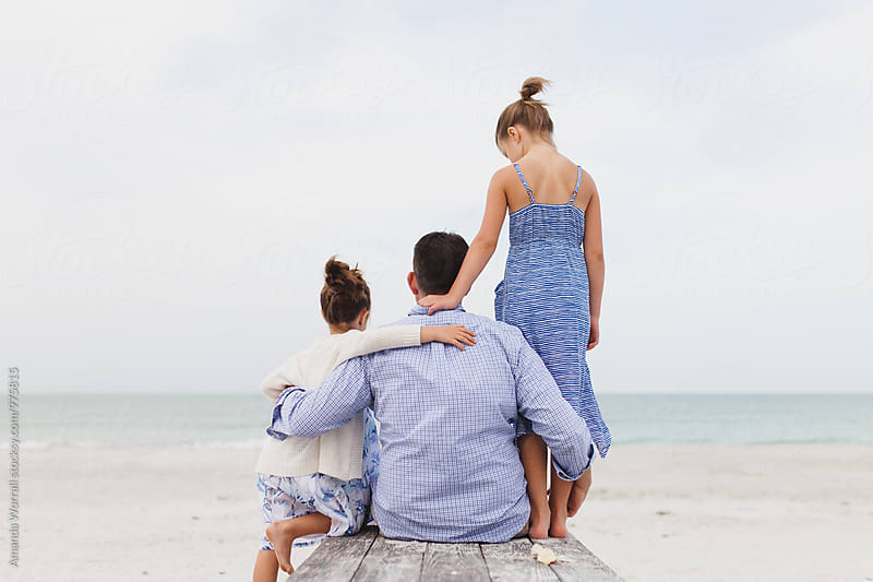A father and his daughters hugging at the beach by Amanda Worrall for Stocksy United