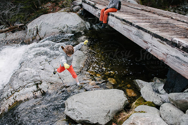 Boy hops from rock to rock across a mountain stream by Cara Dolan for Stocksy United