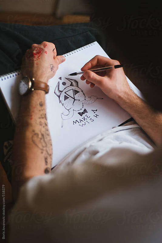 Tattooed illustrator drawing an illustration by Boris Jovanovic for Stocksy United