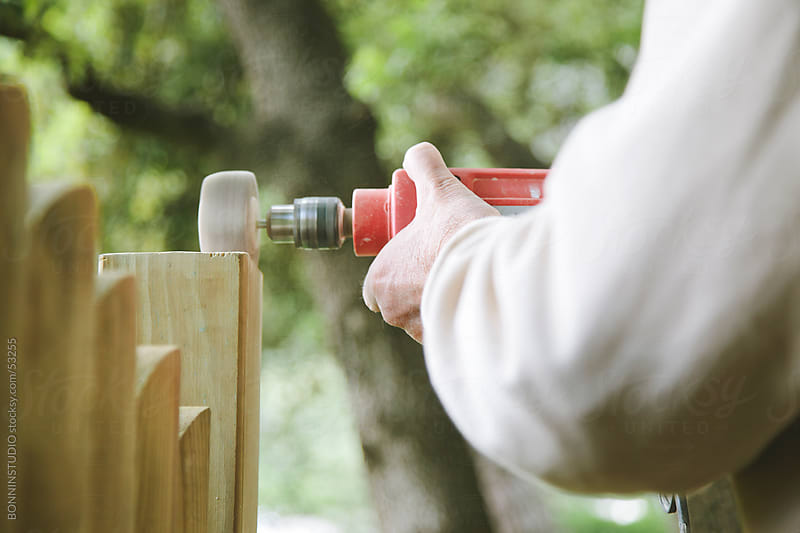 Old man sanding wood in his garden. DIY by BONNINSTUDIO for Stocksy United