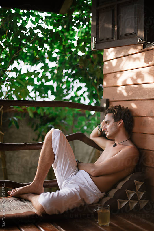 Young man relaxing at the balcony on tropical island by Nabi Tang for Stocksy United