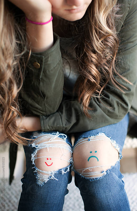 Teenage girl with holes in her jeans and a smiley and a frown drawn on her knees by Carolyn Lagattuta for Stocksy United