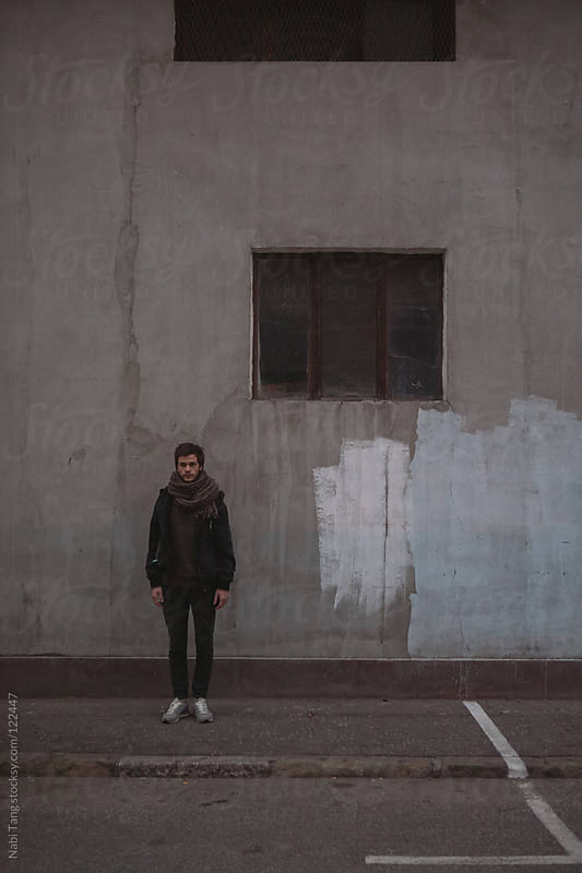 Young handsome guy standing in front of grey wall and small square window by Nabi Tang for Stocksy United