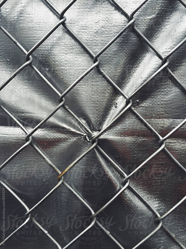 Close up of chain-link fence and silver tarp by Paul Edmondson for Stocksy United
